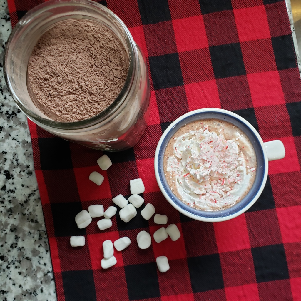 Cup of hot chocolate and jar of mix with mini marshmallows on the side